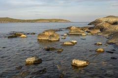 Skały w seashore w zmierzchu w przedpolu, góra i błękitny obrazy stock