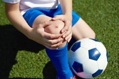 Skada av knäet i pojkefotboll royaltyfria foton