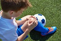 Skada av knäet i pojkefotboll royaltyfria bilder