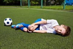 Skada av knäet i pojkefotboll på gräs royaltyfri fotografi