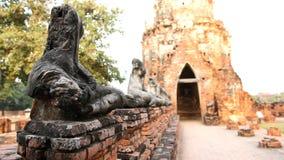 Skada Buddhastatyn, ha suddighet på gammal båge för väggtegelstenport tillbaka Arkivbild
