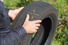 Skada för bilgummihjulet med spikar och den gula fläcken Gummihjul för plan bil i händerna royaltyfri foto