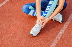 Skada för löparesportben Kvinnan har smärtar i ankel efter genomkörare utomhus på stadion arkivfoto