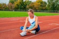 Skada för löparesportben Kvinnan har smärtar i ankel efter genomkörare utomhus på stadion fotografering för bildbyråer