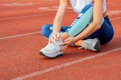 Skada för löparesportben Kvinnan har smärtar i ankel efter genomkörarenolla arkivfoton