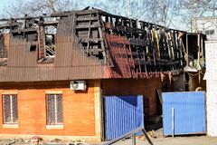 Skada till taket från branden Tegelstenhus som är skadat vid brand man som kontrollerar brandeldsläckaren arkivfoton