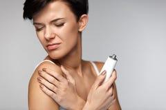Skadabehandling Den härliga kvinnan med armen smärtar och att applicera kräm arkivbild
