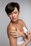 Skadabehandling Den härliga kvinnan med armen smärtar och att applicera kräm royaltyfri fotografi