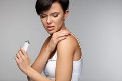 Skadabehandling Härlig kvinnakänsla smärtar och att applicera kräm arkivfoton