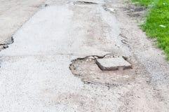 Skadad asfaltväg med djupa hål Royaltyfri Fotografi