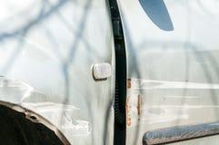 Skadad bil för silver med buckliga aluminum den skrapade metallkroppen och skalningsmålarfärg Royaltyfri Bild