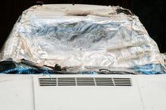 Skadad bil med den brutna och splittrade vindrutan eller vindrutan som täckas med nylon för att skydda medelinre från regn som är Royaltyfria Bilder