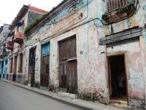 SKADAD FASAD OCH EN KVINNA SOM RINGER, HAVANNACIGARR, KUBA Royaltyfri Fotografi
