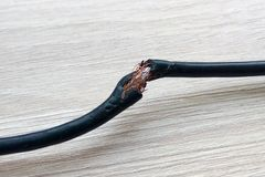 Skadad svart elektrisk kabel p? tr?tabell- eller golvbakgrund Farlig bruten elektrisk kabel arkivbilder