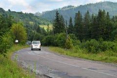 Skadad väg i Carpathian berg, i Ukraina Sprucken asfaltblacktop med gropar Sommarlandskap, skog, himmel Arkivbilder
