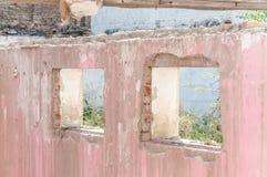 Skadade fönster och vägg av det inhemska civila huset eller byggnad med hålet och det kollapsade taket som förstörs av granaten i royaltyfri fotografi
