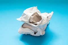 Skadat polyetylenkuvert på blå bakgrund Plast- post- posta påsar royaltyfri foto