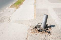Skadat slag för pol för säkerhet för metall för barriär för vägtrafik med den förvridna snabba bilen i olycka och royaltyfria bilder