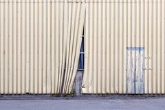 Skadat staket, som döljer bak det oavslutade objektet royaltyfri foto