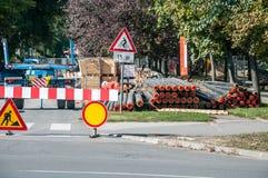 Skadestånd och rekonstruktion för stadsfjärrvärmerörledning som är parallella med gatan med konstruktionsmaskineri och säkerhetsv royaltyfria bilder