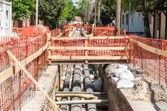 Skadestånd och rekonstruktion för stadsfjärrvärmerörledning som är parallella med gatan med orange konstruktionssäkerhetsnät elle Royaltyfria Foton