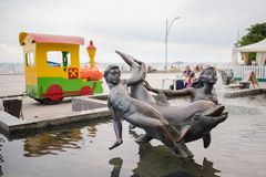 Skadovsk,乌克兰- 2017年6月20日:在水的纪念碑:有海豚的,江边,集合孩子 免版税库存图片
