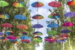 Skadovsk, Ucrânia - 23 de junho de 2017: Guarda-chuvas coloridos que penduram na avenida principal da cidade Fotografia de Stock Royalty Free