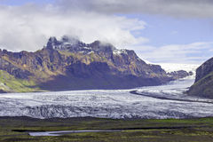 Skaftafellsjokul glacier, Iceland. Wide view of Glacier from a distance with cloud blanketed peaks behind and colorful vegetation in front royalty free stock image