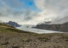Skaftafellsjokullgletsjer: de gletsjertong met ijs en de sneeuw glijden onderaan de bergvallei in Skaftafell, Zuid-IJsland, Europ stock foto