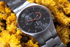 Skagen wristwatch. Milan, Italy - 2019, May 18 : A Skagen metal silvery wrist watch with chronometer on yellow flowers royalty free stock image