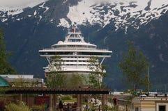 SKAGWAY, ALASKA, JUN 26 2012: Het schip van prinsesCruise voor sneeuw afgedekte bergen wordt gedokt die Stock Foto's