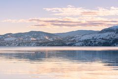 Snow-covered mountains and sunset colors reflected in still waters of lake in winter stock photo