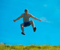Skakać w górę faceta tła niebieskie niebo Pod zieloną trawą Obraz Stock