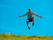 Skakać w górę faceta tła niebieskie niebo Pod zieloną trawą Zdjęcie Royalty Free