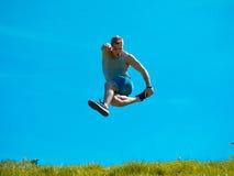 Skakać w górę faceta tła niebieskie niebo Pod zieloną trawą Fotografia Royalty Free