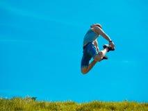 Skakać w górę faceta tła niebieskie niebo Pod zieloną trawą Fotografia Stock