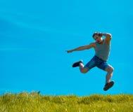 Skakać w górę faceta tła niebieskie niebo Pod zieloną trawą Obrazy Stock