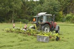 Skaka av det mejade gräset med den röda traktoren med Ted Arkivfoton