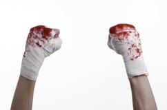 Skakade hans blodiga hand i en förbinda som var blodig förbinder, kampklubban, gatakampen, det blodiga temat, vit bakgrund som is Arkivfoton