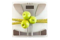 Skala mit einem messenden Band und einem Apfel Stockbilder