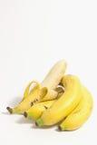 Skalad banan nära en klunga av mogna bananer på vit bakgrund royaltyfri fotografi