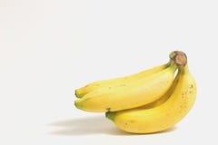Skalad banan nära en klunga av mogna bananer på vit bakgrund royaltyfri bild