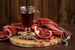 Skalad granatäpple, exponeringsglas av granatäpplefruktsaft och jewerly på wo Arkivfoto