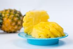 Skalad och skivad ananas på en platta Royaltyfri Fotografi