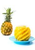 Skalad och skivad ananas på en platta Royaltyfri Bild