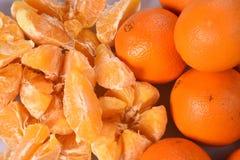 Skalade apelsinskivor och nya ljusa orange apelsiner på hög Arkivfoto