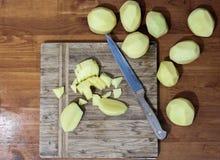 Skalade potatisar skivade ‹för †på ett bräde royaltyfri foto