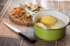 Skalade rå potatisar i vattnet som är klart för att laga mat arkivbilder