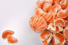 Skalade skivor för apelsin är nytt av mandariner med vita åder på en vit bakgrund, på vänstert två separata skivor, ett tomt utry Arkivfoton