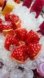 Skalar granatäpplet på is med flaskan av fruktsaft arkivfoton